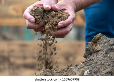 Sifting with hands and pouring dirt and sand at field