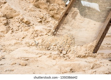 Sifting sand through a grid at a construction site.