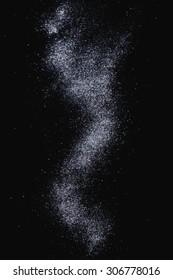 Sifting sugar powder over black background.