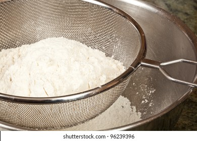 Sifting white flower through a sieve
