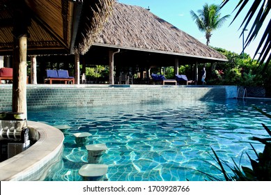 Sigatoka, Fiji - 2017: A swim-up pool bar in a turquoise swimming pool. Traditional Fiji bure thatched style roof. At the Outrigger Fiji Beach Resort.