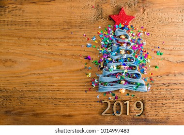 Sigh symbol Christmas Tree from a lot colorful confetti, lace and red star toy on old retro vintage style wooden texture background Empty copy space for inscription Idea of merry new year 2019 holiday