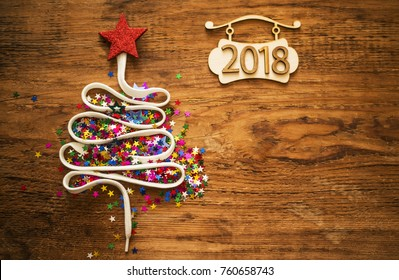 Sigh symbol Christmas Tree from a lot colorful confetti, lace and red star toy on old retro vintage style wooden texture background Empty copy space for inscription Idea of merry new year 2018 holiday