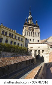 SIGHISOARA, ROMANIA - CIRCA OCTOBER, 2015: Clock tower sided by old building inside medieval town of Sighisoara, Transylvania, Romania