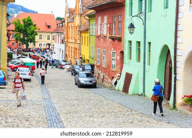 SIGHISOARA, ROMANIA - JULY 17: Unidentified tourists walking in historic town Sighisoara on July 17, 2014. City in which was born Vlad Tepes, Dracula