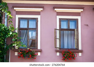 Sighisoara, Romania - June 23, 2013: Pink facade with windows and flowers from Sighisoara city old center, Transylvania, Romania