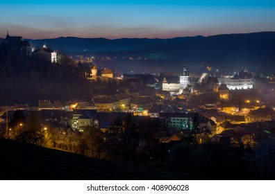 Sighisoara town - night view. Illuminated old buildings are in the composition centre.