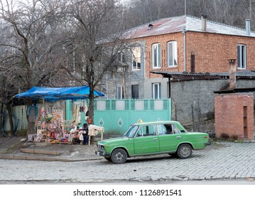 Sighnaghi, Georgia - December 4, 2017 : old russian taxi car and souvenir stall in front of Saint Nino monastery at Bodbe, one of the major pilgrimage sites in Georgia