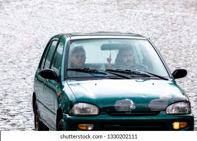 Sighnaghi, Georgia - June 9, 2016: Two people sitting in the car under heavy rain on the street of Sighnaghi.