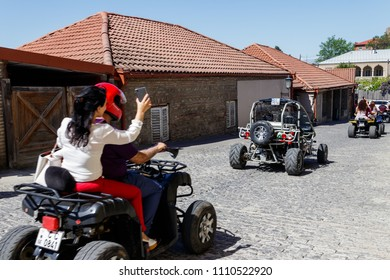 Sighnaghi, Kakheti, Georgia - May 2, 2018: Happy tourists riding all terrain vehicle on street of the medieval town Sighnaghi. Excited young people on quad bikes. Trip on ATV