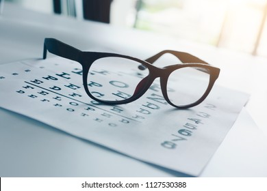 Sight glasses on an optician sight chart on a desk