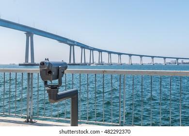 Sightseeing binoculars facing the Coronado bridge in San Diego, California, on a viewing pier at Cesar Chavez Park.
