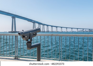 Sightseeing binoculars on the Cesar Chavez Park viewing pier, overlooking the San Diego bay and the Coronado bridge.