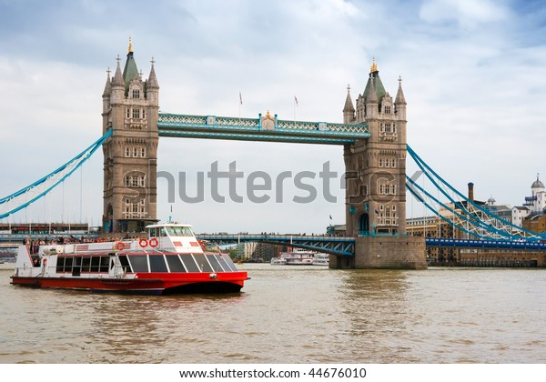 A sightseeing boat goes near the Tower Bridge. London, England