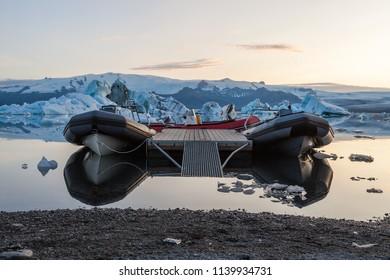 Sightseeing boat tied down near the shore. Scattered melting icebergs in Jokulsarlon glacier lagoon. Base of the Vatnajokull glacier at Jokulsarlon, Iceland.