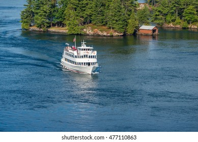 Sightseeing cruise ship in Thousand Islands on St. Lawrence river passing an island with a boathouse