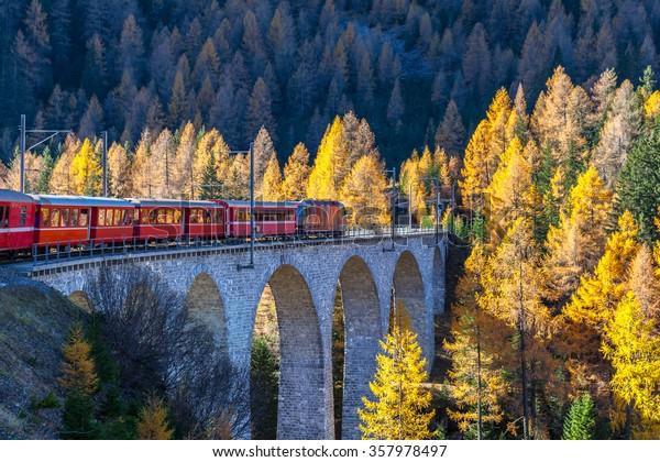 El tren turístico bernina express del ferrocarril Rhaetian corriendo en el Viaducto con vistas a los coloridos árboles en un soleado día de otoño, Cantón de Grisons, Suiza