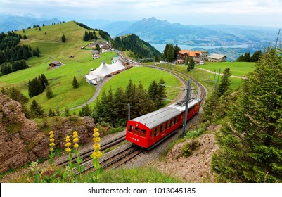A sightseeing train traveling on the cogwheel railway through green grassy meadows on Mt. Rigi, with rugged Pilatus peaks among majestic mountains in background on a cloudy summer day in Switzerland