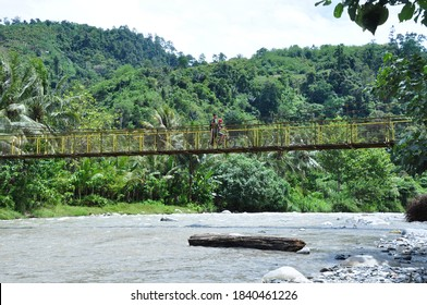 Sigi, Central Sulawesi, Indonesia - October, 2020: People crossing the hanging bridge in Sigi, Indonesia. The bridge is importance for development in rural area.