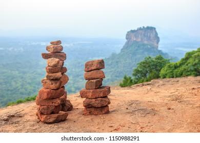 Sigiriya rock in Sri Lanka, with stacks of stones in foreground.