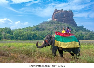 SIGIRIYA, SRI LANKA – 14 JULY 2017: Tourists riding on an Elephant tour around Sigiriya rock on July 14 2017 In Sgiriya, Sri Lanka.  An Elephant tour around Sigiriya is  popular among the tourists