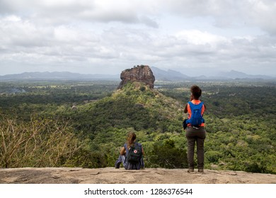 Sigiriya, Sri Lanka - August 17, 2018: Two tourists admiring the Lion Rock in the distance