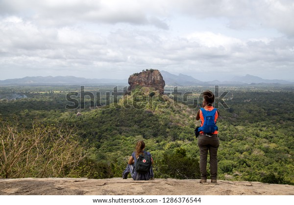 Sigiriya, Sri Lanka - August 17, 2018: Two tourists admiring the Lion Rock in the distance