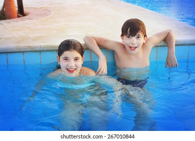 siglings boy and girl play in open air swimming pool at the egyptian sea resort hotel