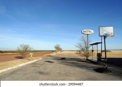 Sign for an abandoned motel on a desert road in rural Texas, with basketball court