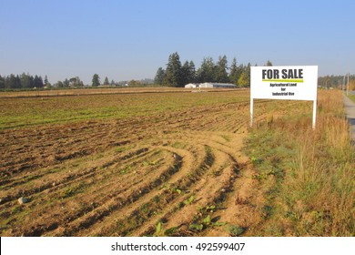 A sign advertises agricultural land for industrial use for sale/Agricultural Land for Industrial Use/A sign advertises agricultural land for industrial use for sale.