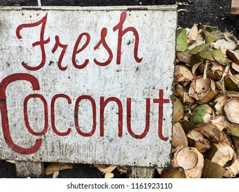 A sign advertising Fresh Cocunut is located next to a pile of coconut husks that have already been cut open.