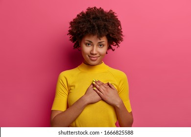 Sign of affection and admiration. Pretty curly woman presses palms to heart, being grateful for gift, wears yellow t shirt, poses over rosy background, says you are always in my heart, smiles gently