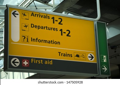 Sign at airport with arrivals and departures as well direction to trains and first aid
