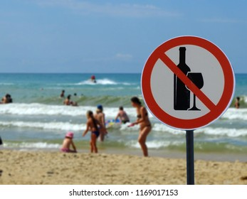 Sign alcohol is prohibited on the beach against the background of bathing people in the sea.