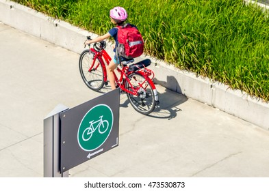 Sign along a Bicycle Path with a Child Cycling in Background. Shallow Deep of Field.