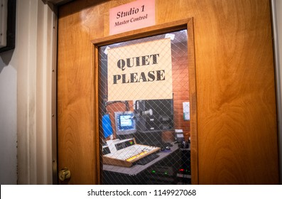 """A sign asks for """"quiet please"""" outside of a radio station master control room."""