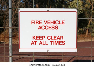A sign attached to a metallic wire fence or gate reads: Fire Vehicle Access - Keep Clear At All Times.