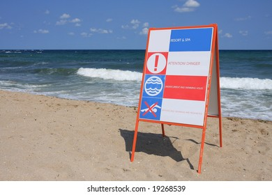 """Sign """"Attention! Danger"""" on the beach."""