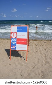 """Sign """"Attention! Danger"""" on the beach and man in the water."""