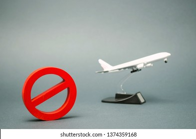 The sign of the ban and a miniature toy aircraft. Ban on flights of civil aircraft. Forbidden zone. Stop symbol. Bans on airport construction. Plane. Night flights. Law. Prohibition