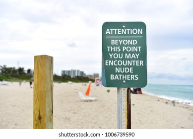 Sign in the beach with attention about clothing