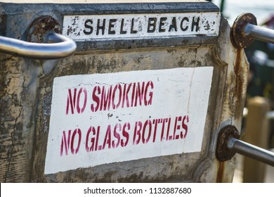 A sign at the beach prohibiting smoking and having glass bottles on the beach.