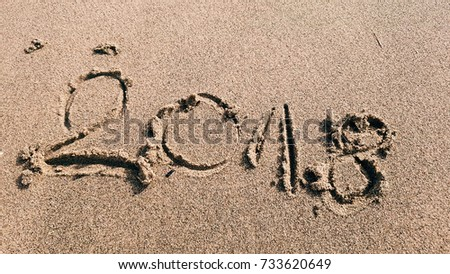 sign in beach sand saying 2018 denoting a new year