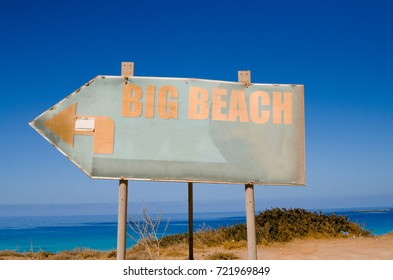 Sign for the beach and sea background. Close view of arrow sign direction with text: big beach.