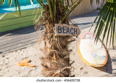 Sign beach with surf board and sandals