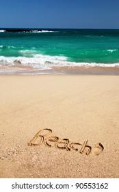 "Sign ""Beach"" written in the sand of the tropical beach of Sri Lanka near the azure sea"