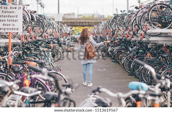 """Unterschreiben: """"Vorsicht, schieben Sie Ihr Fahrrad stehen, bis es verschlossen ist"""". Rückansicht des Mädchens verlor ihr Fahrrad auf dem Fahrradparkplatz in Eindhoven City (Niederlande) - Fahrradchaos in Holland Konzept"""