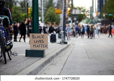 """A sign """"black lives matter"""" left behind at a rally, blurred crowd behind the the sign, protest happening in the blurred background"""