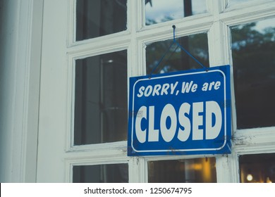A Sign board of sorry we are closed hang on door of business shop with nature green background