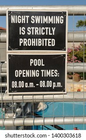 Sign by a European holiday swimming pool warning that swimming during the night is strictly prohibited.